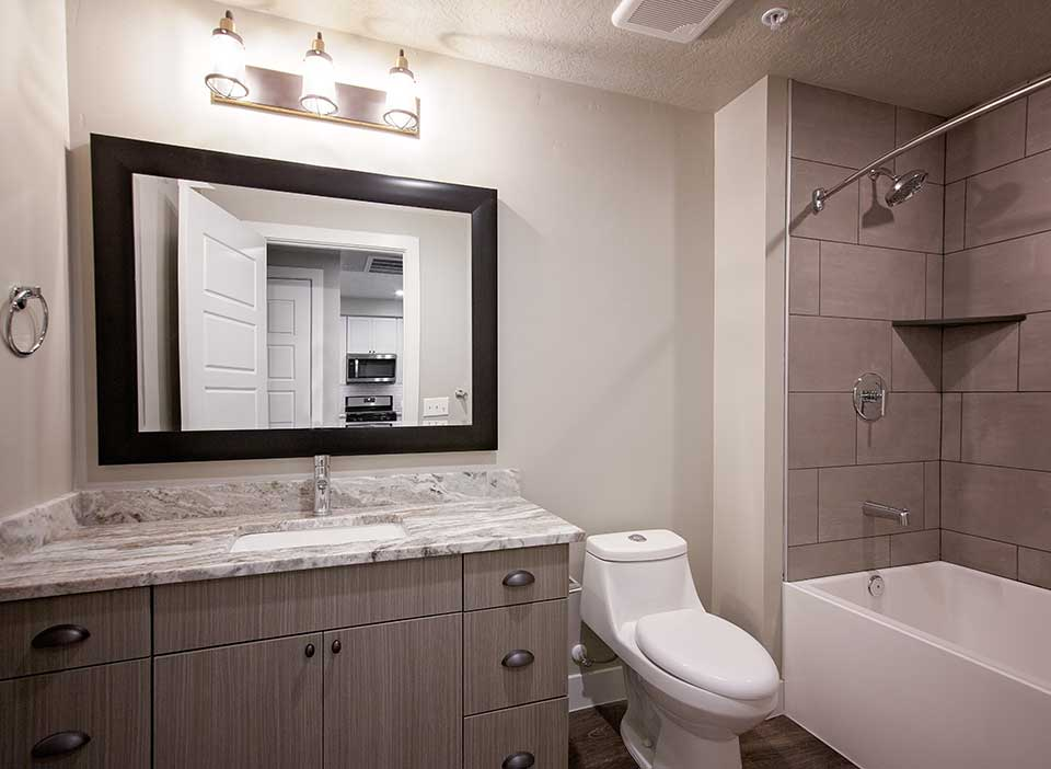Bathroom with smooth stone countertops, tiled shower and rich wood floors.
