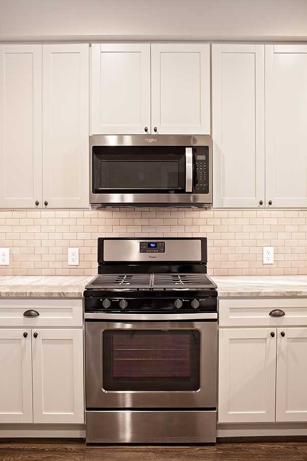 Stainless steel gas range, oven, and microwave, painted cabinets and smooth stone countertops.
