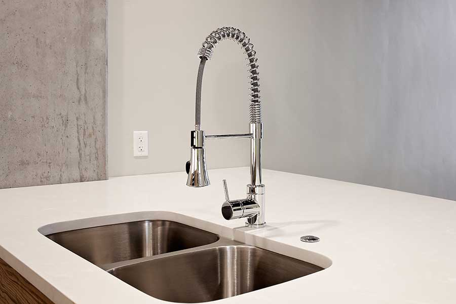 Dual basin undermount stainless steel sink with tall gooseneck faucet.