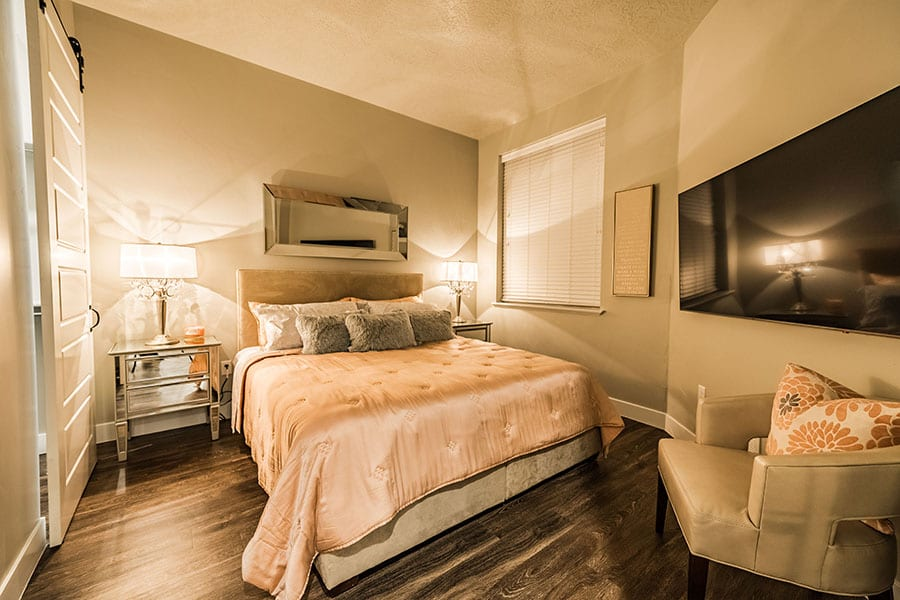 Warm bedroom with large bed, metallic bedside tables with lamps, large television, and a plush leather chair.