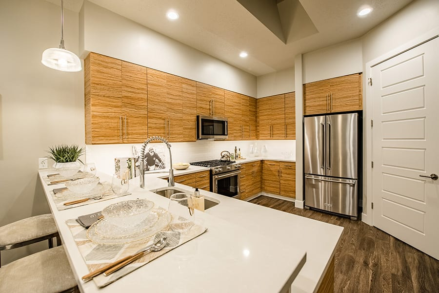 Kitchen with wood cabinets and floors, smooth countertops, and large french door stainless steel refrigerator.