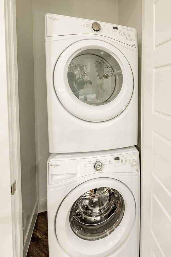 Stacked set of washer and dryer inside closet.