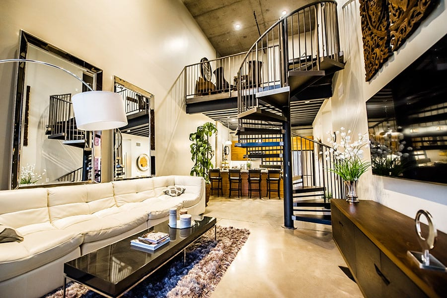 Loft apartment with long comfortable couch, modern wooden console and coffee table, and metal spiral staircase.