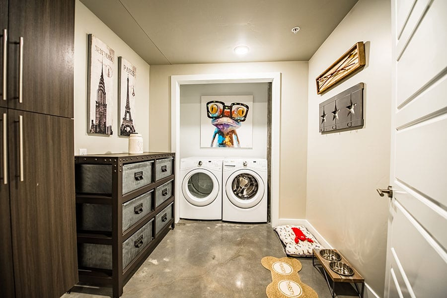 Laundry room with washer and dryer, large industrial style drawers, and polished concrete floors.