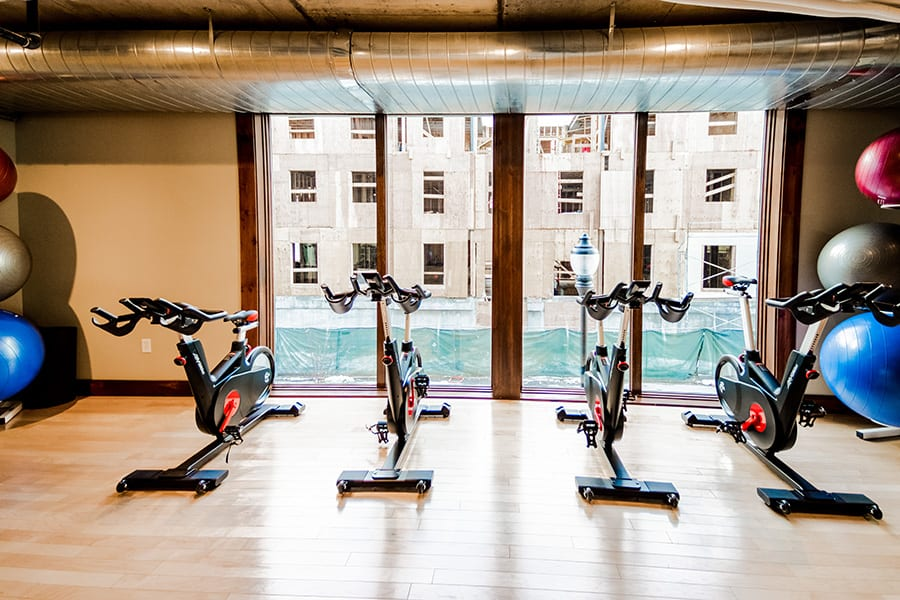 Fitness center with wood floors, four spin bicylces, and floor to ceiling windows.