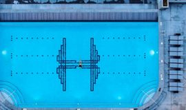 Overhead view of person swimming in large Hardware District rooftop swimming pool.