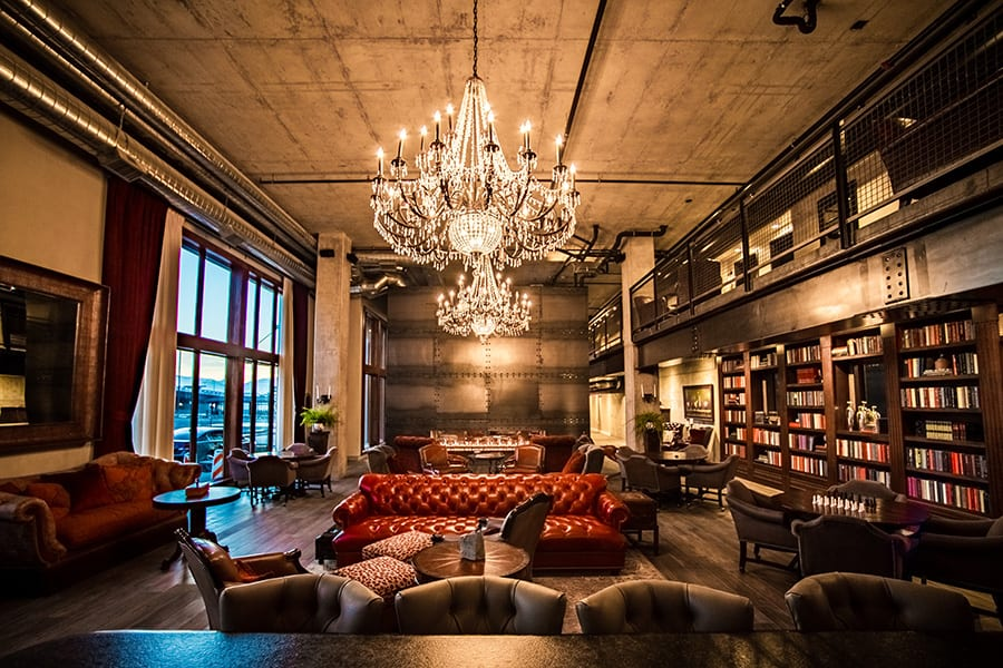 Clubroom with large plush couch, glowing chandeliers, tall windows and a bookshelf wall.