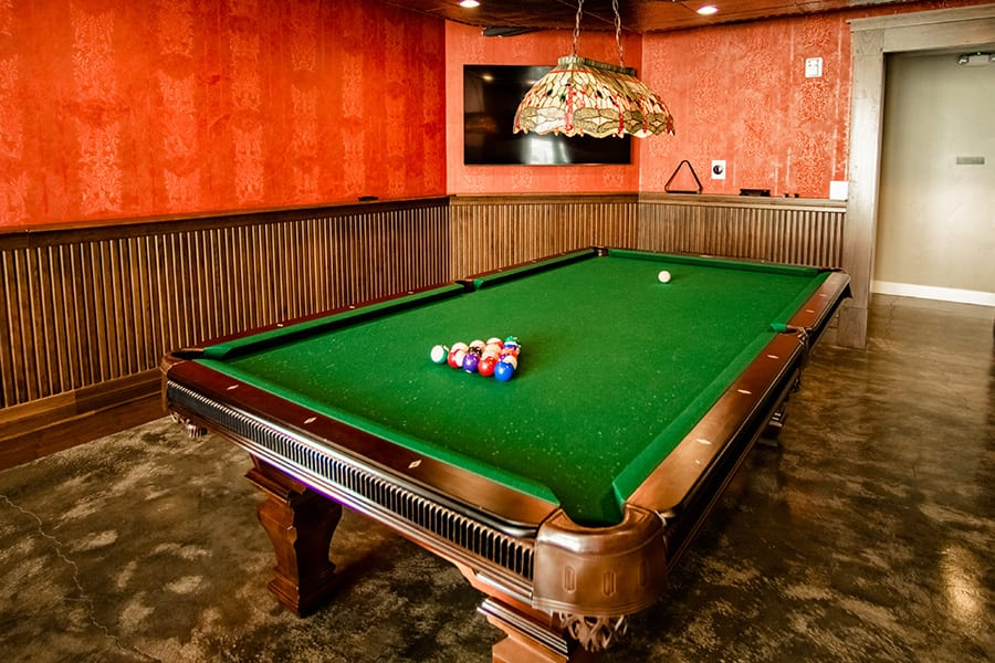 Game room with polished concrete floors, wood panels, and large pool table with lamp.