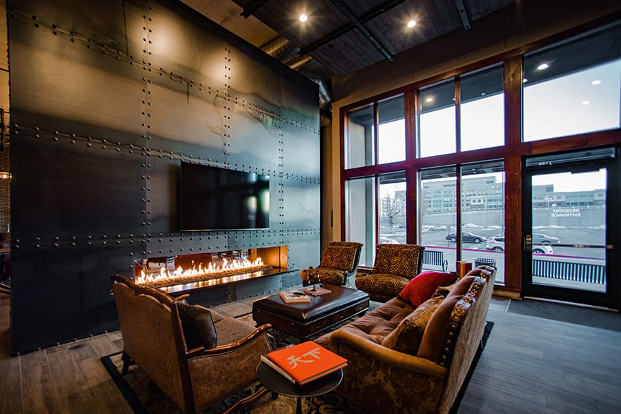 Clubroom space with large windows, plush couches, and a large TV mounted on a riveted metal wall.