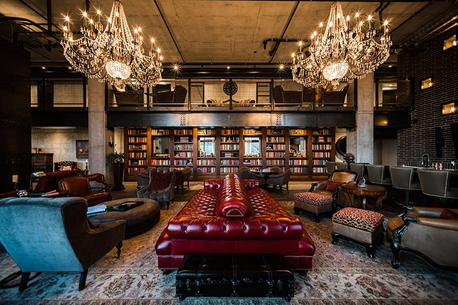 Clubroom with large plush double sided couch, glowing chandeliers, and a bookshelf wall.