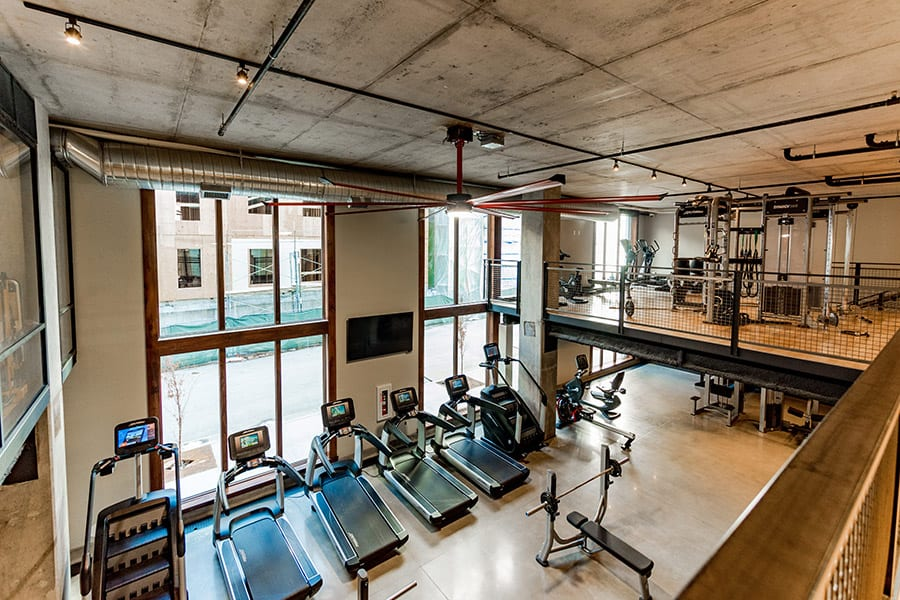 Fitness center from second story looking down on treadmills and stair steppers with large floor to ceiling windows.