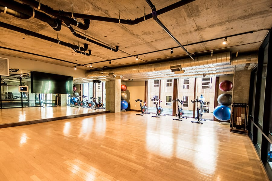 Large fitness studio with wood floors, spin bicycles, and full length wall mirrors.