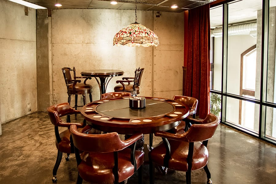 Game room with large windows, hanging stained glass lamp and poker table.