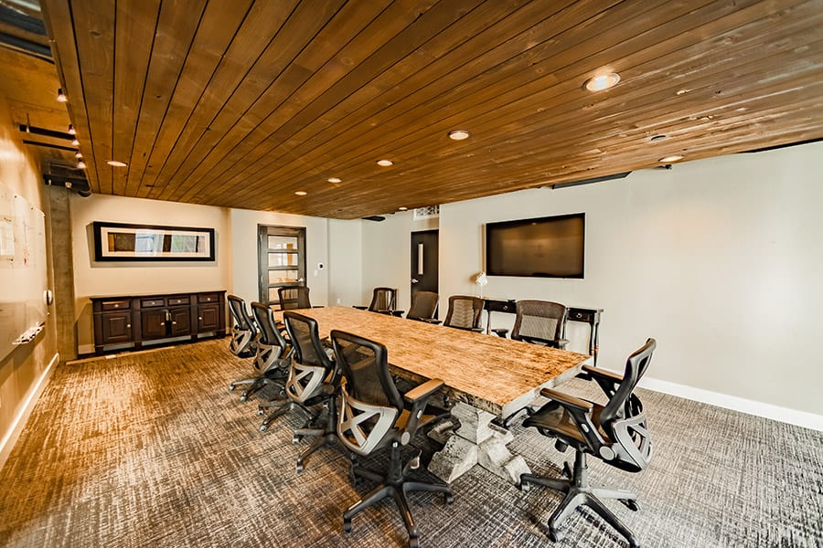 Conference room with large stone table, carpeted floors, and rich wood ceiling with recessed lights.