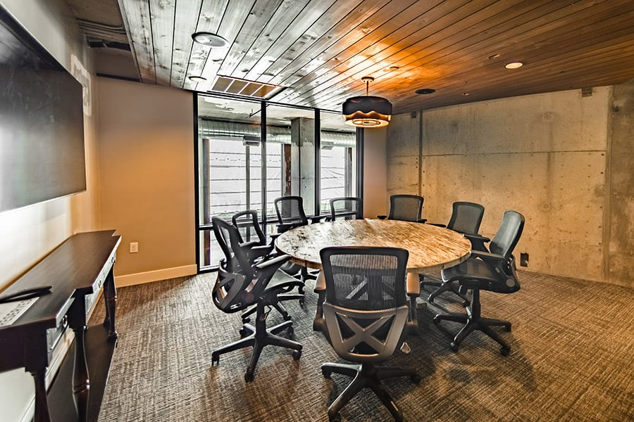 Conference room with circular stone table, concrete walls, and rich wood ceiling.