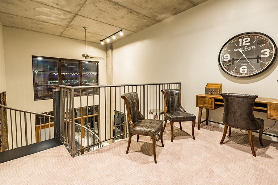 Second story of loft apartment with vintage wooden desk, leather chairs and metal spiral staircase.
