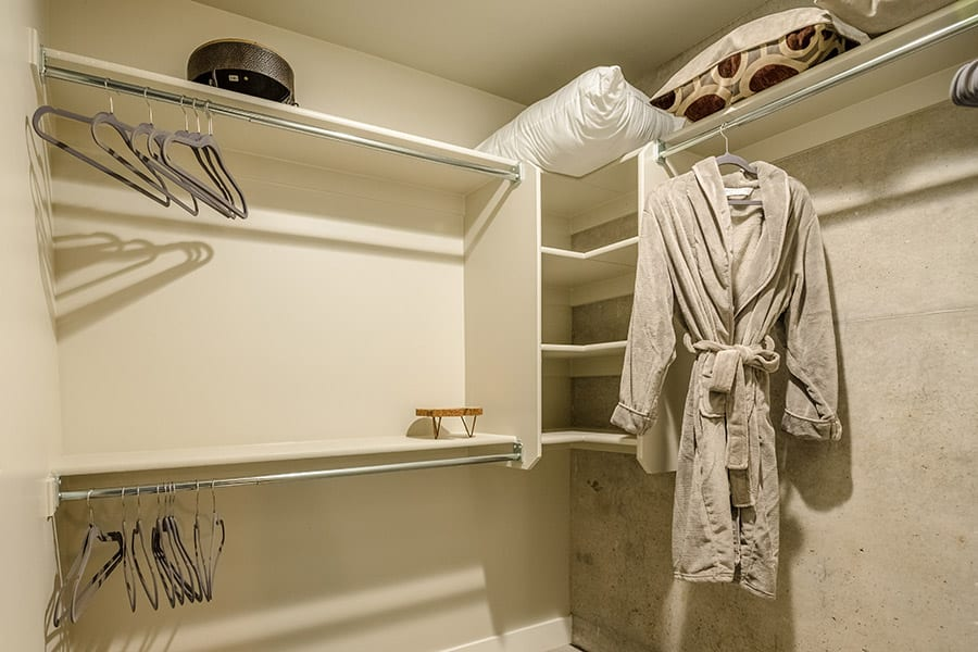 Walk in closet corner with clothing rods, shelves, stored bedding and a robe.