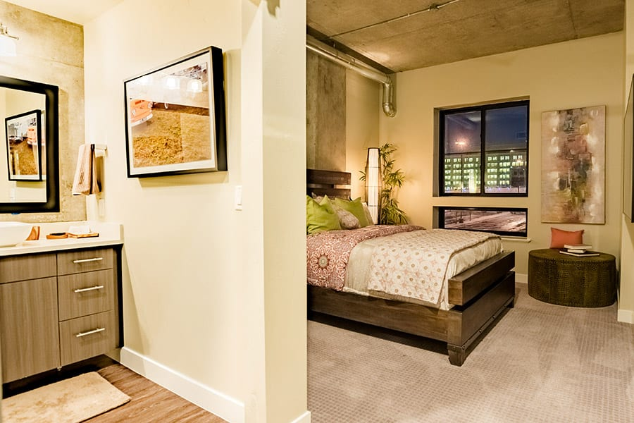 Master bedroom and bathroom with wood drawers, wood platform bed, and city facing square window.