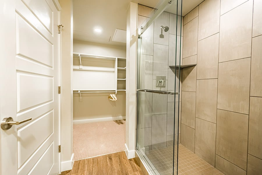 Bathroom and closet with large tiled shower, sliding glass doors and wood floors.