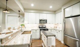 Kitchen with stainless steel gas range and microwave, tiled backsplash, and smooth countertops.