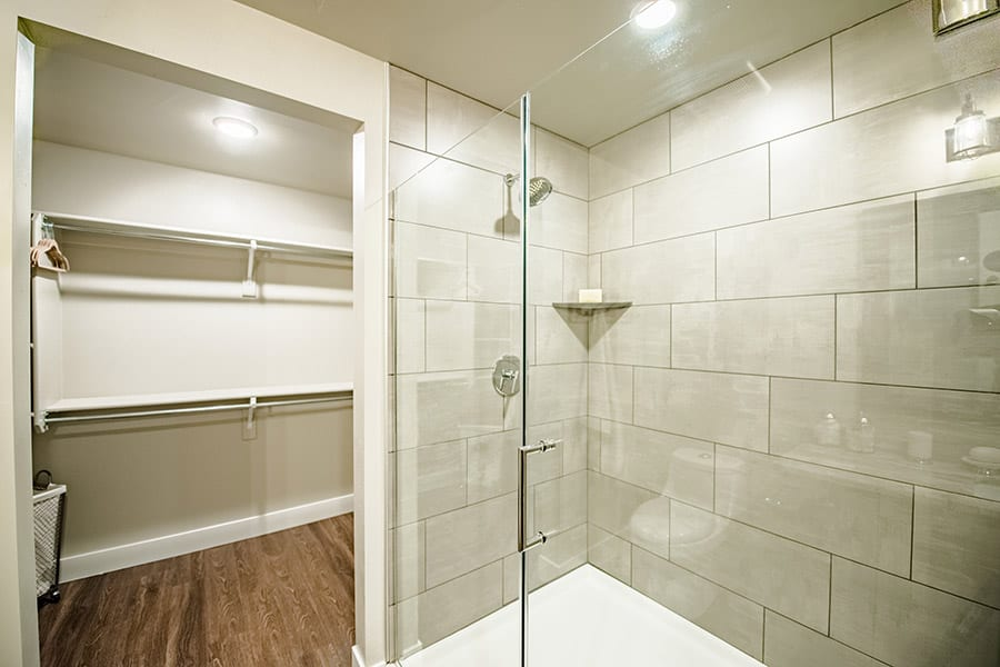 Bathroom with large tiled shower, sliding glass doors, and wood floors opening to walk in closet.