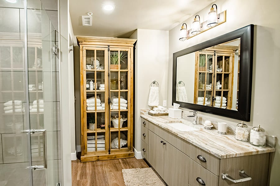 Bathroom with wood floors, glass shower doors, and large wood cabinet with linens and decorations.