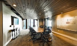 Conference room with stone table, floor to ceiling windows and rich wood ceiling.