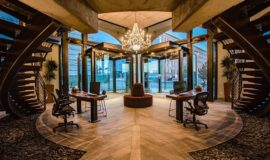 Grand entrance hall with curved dual staircases, wood and stone floors, and glowing glass chandelier.