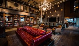 Clubroom with plush double sided couch, rich wood floors with rugs, and glowing chandeliers.