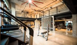 Fitness center with weight benches, treadmills, stair stepper, and rotating rock climbing wall.